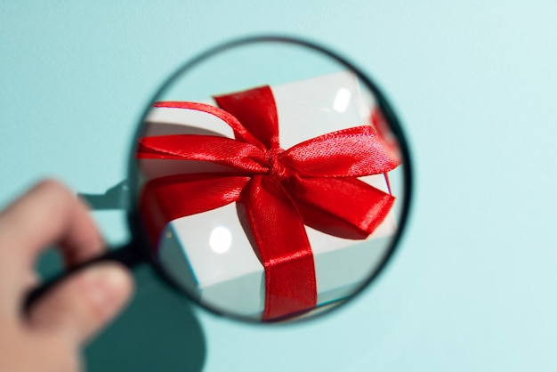 Białe pudełko z czerwoną kokardką powiększone przez lupę trzymaną ręcznie.