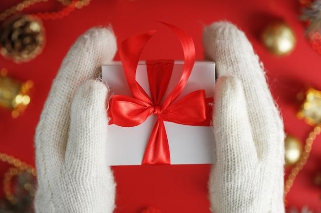 Białe pudełko z czerwoną kokardką w rękawiczkach. prezent na boże narodzenie lub nowy rok. dziewczyna w dzianinowych rękawiczkach z prezentem i dekoracjami noworocznymi, boże narodzenie, nowy rok, koncepcja urodziny.