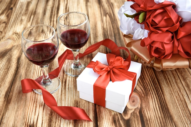 Białe pudełko z czerwoną satynową kokardką, dwa kieliszki wina i bukiet czerwonych i białych kwiatów sztucznych róż na drewnianym tle.