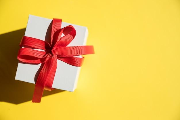 Białe pudełko z czerwoną wstążką i kokardą