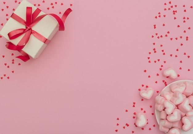 Białe pudełko z czerwoną wstążką i piankami w kształcie serca w białej misce na różowym tle