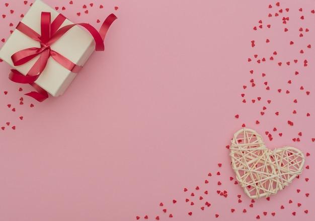 Białe pudełko z czerwoną wstążką i rattanowym sercem na różowo