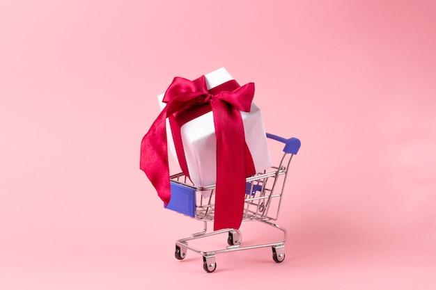 Białe pudełko z czerwoną wstążką w koszyku na zakupy. koncepcja zakupów upominkowych, sklep internetowy