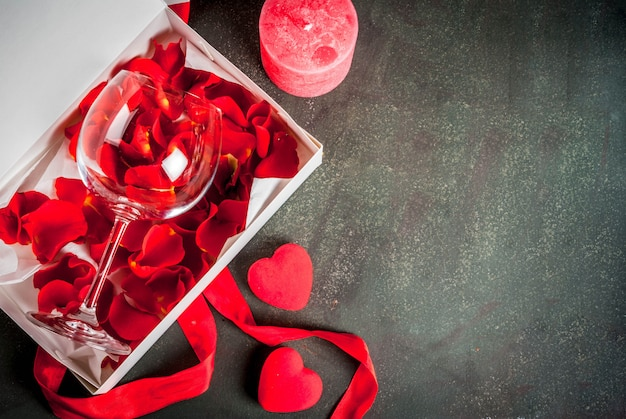 Białe pudełko z czerwoną wstążką, z płatkami róży w kieliszku do wina