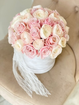Białe pudełko z delikatnymi różowymi różami i ranunculi na krześle. luksusowy bukiet kwiatów na świąteczny prezent. piękne kwiaty ślubne