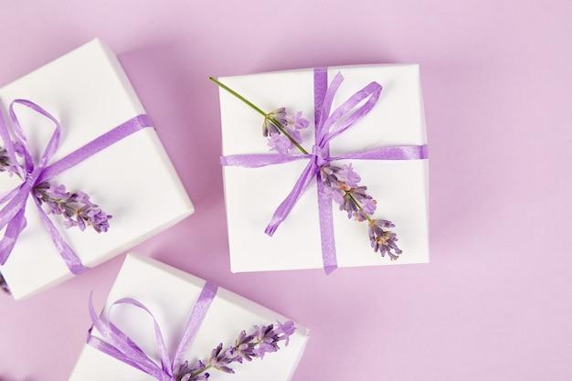 Białe pudełko z fioletową wstążką i lawendą