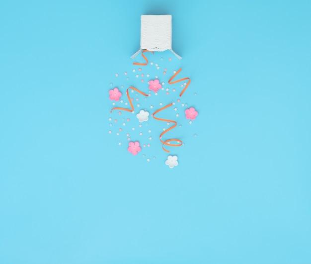 Białe pudełko z imprezowym konfetti, serpentyny i eksplozją kwiatów na niebieskim tle.
