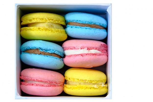 Białe pudełko z kolorowymi makaronikami francuskich słodkich ciast. do reklamy w kawiarni lub piekarni.