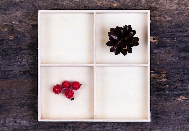 Białe pudełko z przegródkami na drewnianym tle wypełnionym stożkiem drzewa i jagodami jarzębiny