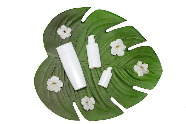 Białe puste butelki bez napisu wśród białych kwiatów na zielonym liściu. flatlay. widok z góry. na białym tle koncepcja kosmetyków naturalnych, pielęgnacja skóry ciała, twarz, salon kosmetyczny spa