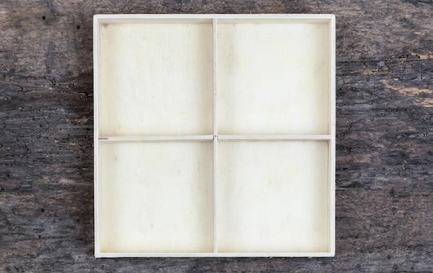 Białe puste drewniane pudełko z przegródkami na drewnianym tle. miejsce na towary w sklepie, biżuterię lub drobne rzeczy