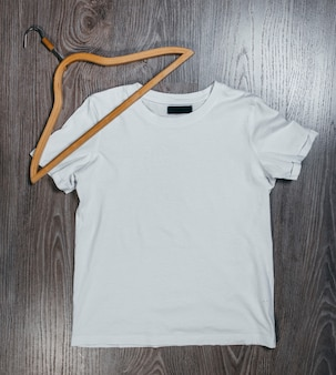 Białe puste koszulki z drewnianym wieszakiem na szarej przestrzeni