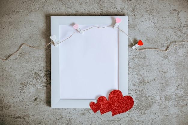 Białe puste miejsce na środku białej ramki z liną na ubrania i papierem w kształcie serca, makieta