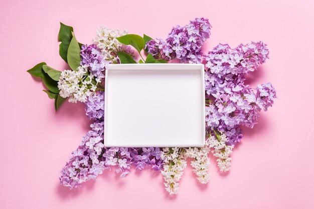 Białe puste pudełko ozdobione kwiatami bzu na różowym tle