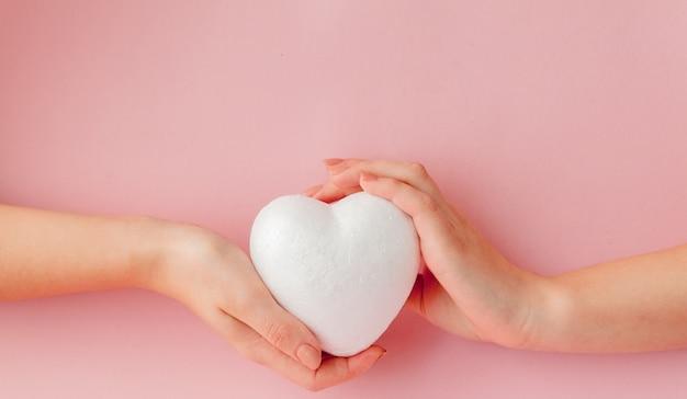 Białe puste serce miłości w ręce