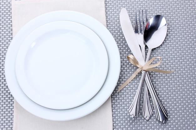Białe puste talerze z widelcem, łyżką i nożem przewiązane wstążką na szarym obrusie