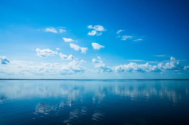 Białe puszyste chmury błękitne niebo nad powierzchnią morza.