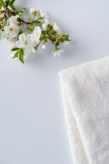 Białe puszyste ręczniki kąpielowe z gałęzi kwitnących wiśni na białej powierzchni. koncepcja spa i pielęgnacji ciała. skład spa. skopiuj miejsce