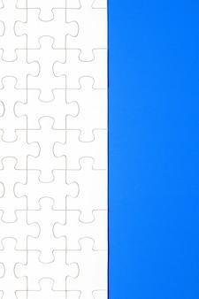Białe puzzle na niebieskim tle. tło dla treści