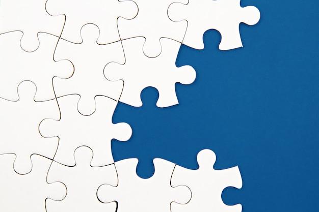 Białe puzzle na niebieskim tle z brakującymi elementami. niekompletne elementy, koncepcja poszukiwania rozwiązania