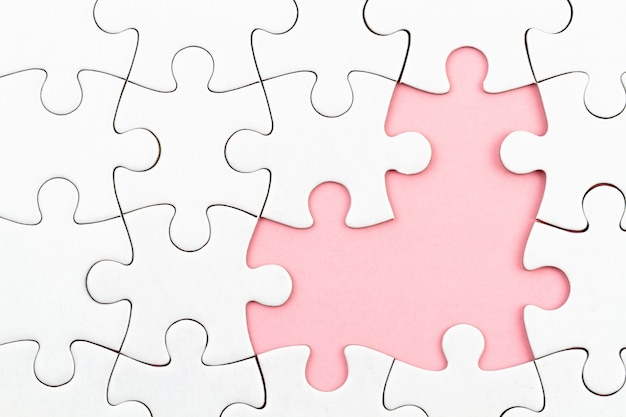 Białe puzzle na różowym tle z brakującymi elementami. niekompletne elementy, koncepcja poszukiwania rozwiązania