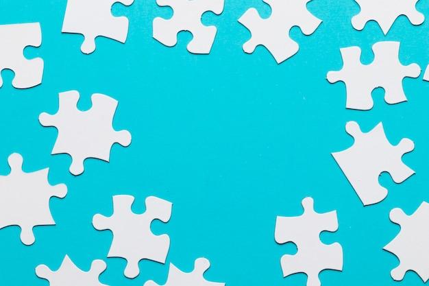 Białe puzzle rozłożone na niebieskim tle