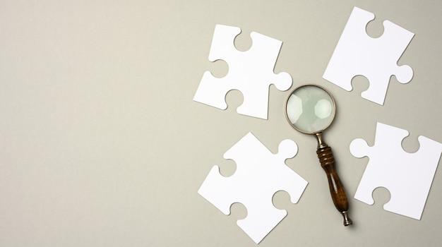 Białe puzzle wokół szkła powiększającego na szarym tle. koncepcja poszukiwania utalentowanych osób, rekrutacja personelu, identyfikacja zdolnych do awansu zawodowego