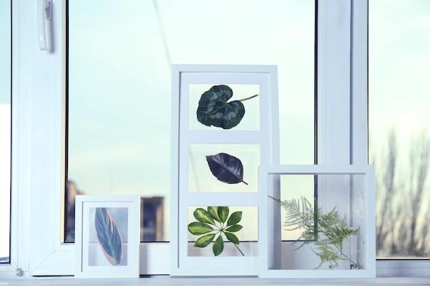 Białe ramki z zielonymi liśćmi na parapecie