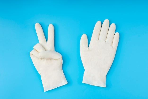 Białe rękawiczki lateksowe. koncepcja ochrony. przy odpowiedniej ochronie pokonujesz wirusa.