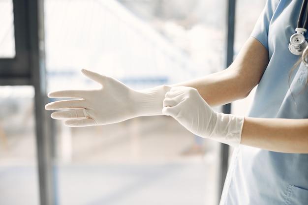 Białe rękawiczki. lekarka. kobieta przy oknie