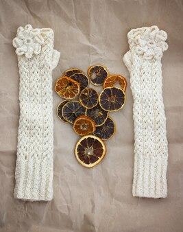 Białe rękawiczki, suszone plastry pomarańczy i różowe serce na tle papieru.