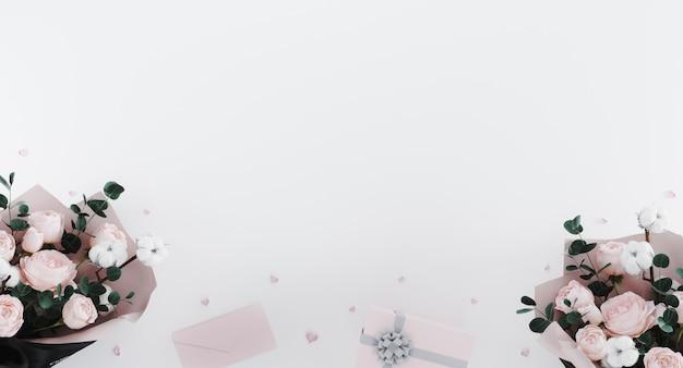 Białe romantyczne tło z bukietami piwonii, konfetti w kształcie serca, listu i białe pudełko z różową wstążką.