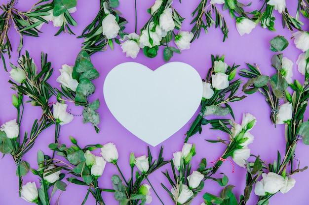 Białe róże i kształt serca na fioletowym tle. powyżej widok