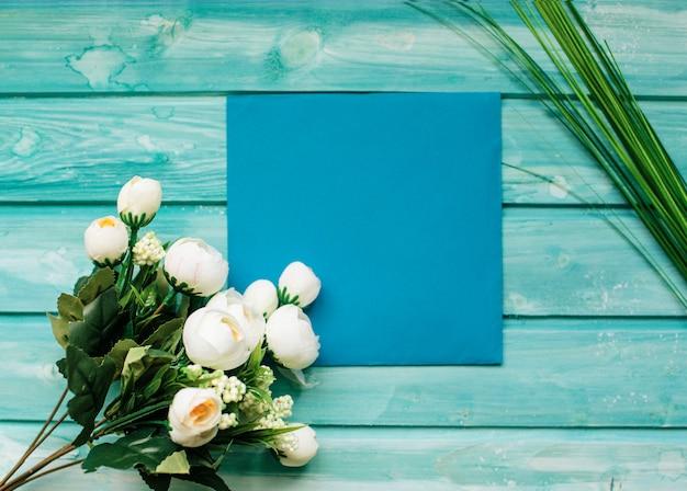 Białe róże i niebieska koperta