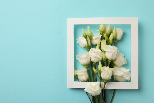 Białe róże i ramka na niebieskim tle