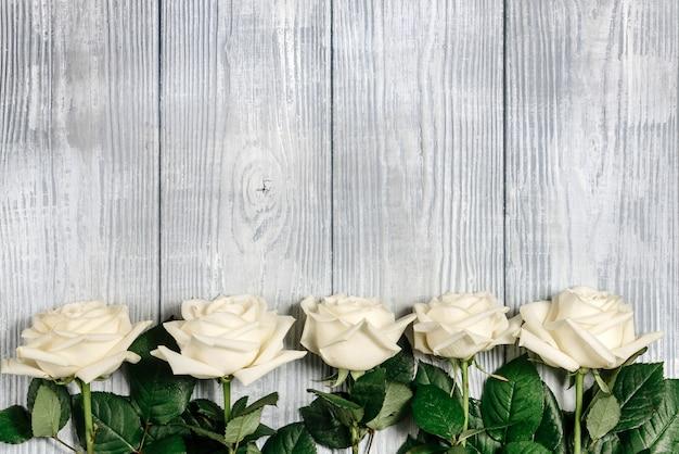 Białe róże leżą na skraju jasnego drewnianego tła