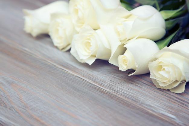 Białe róże na drewnianym tle