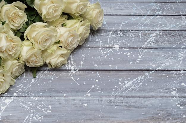 Białe róże na szarym drewnianym tle. skopiuj miejsce
