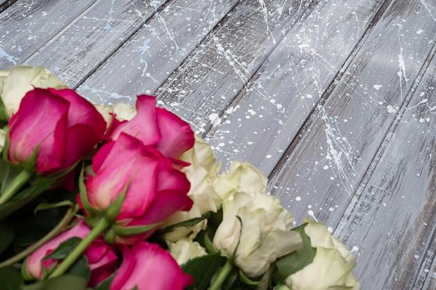 Białe róże na szarym i różowym tle.
