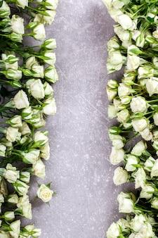 Białe róże na szarym tle. świeże, małe kwiaty z kroplami wody