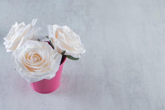 Białe róże w różowym wiadrze, na białym stole.