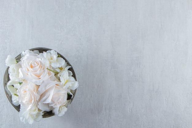 Białe róże w żelaznej misce, na białym stole.