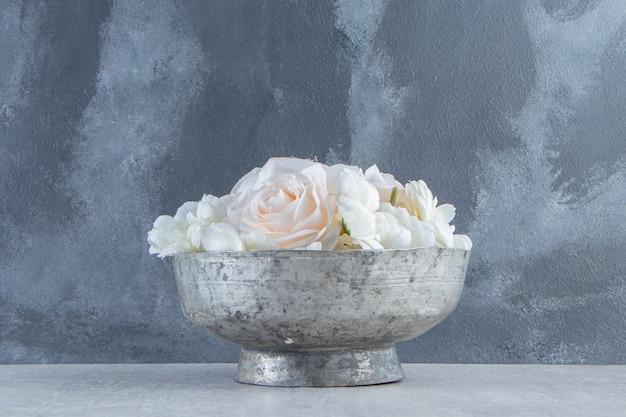 Białe róże w żelaznej misce, na białym tle.