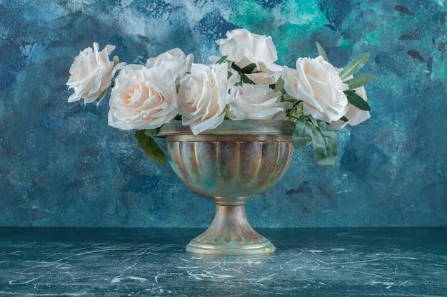 Białe róże w żelaznej misce, na niebieskim tle.