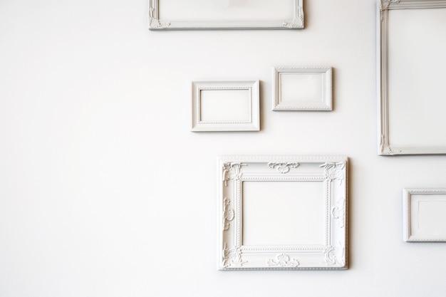 Białe różne antyczne puste ramki na zdjęcia lub zdjęcia na białej ścianie nowoczesny design, minimalistyczny wystrój wnętrz, miejsce na kopię lub miejsce na tekst z bliska