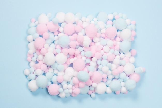 Białe, różowe i niebieskie miękkie pompony jako tło. jasne tło.
