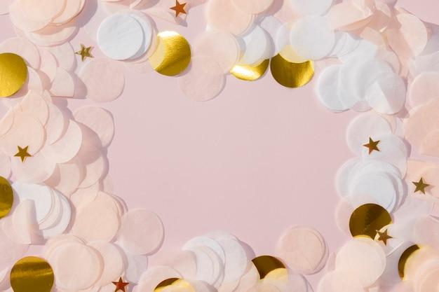 Białe różowo-złote papierowe konfetti z gwiazdami na pastelowo różowej ramce z miejscem na kopię na dowolny projekt świąteczny
