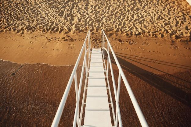 Białe schody prowadzą na plażę z łodzi
