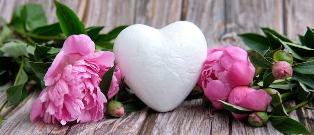 Białe serce stoi otoczone różowymi pąkami piwonii na drewnianym tle
