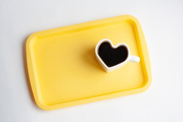 Białe serce w kształcie filiżanki kawy na żółtej tacy, na białym tle, widok z góry